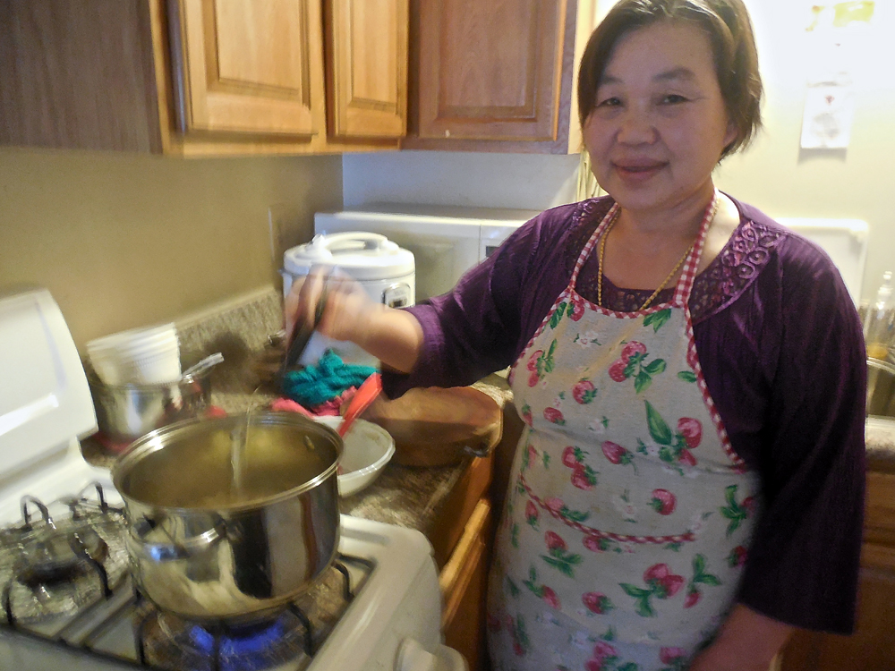 Cho Mei's mother, Naw Htoo prepares a traditional Karen soup with chicken, lemongrass, cilantro and spices at their home in Oakland. Photo: Shuka Kalantari