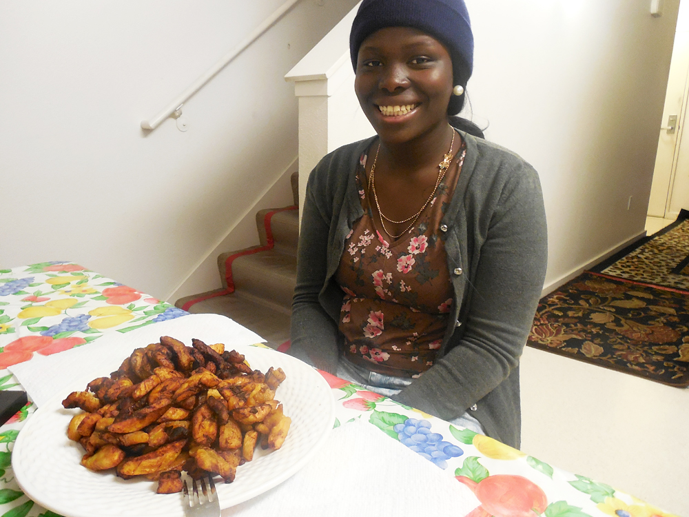 Patience Wilson proudly poses in front of the plantain dish she will prepare for Christmas dinner. Photo: Shuka Kalantari