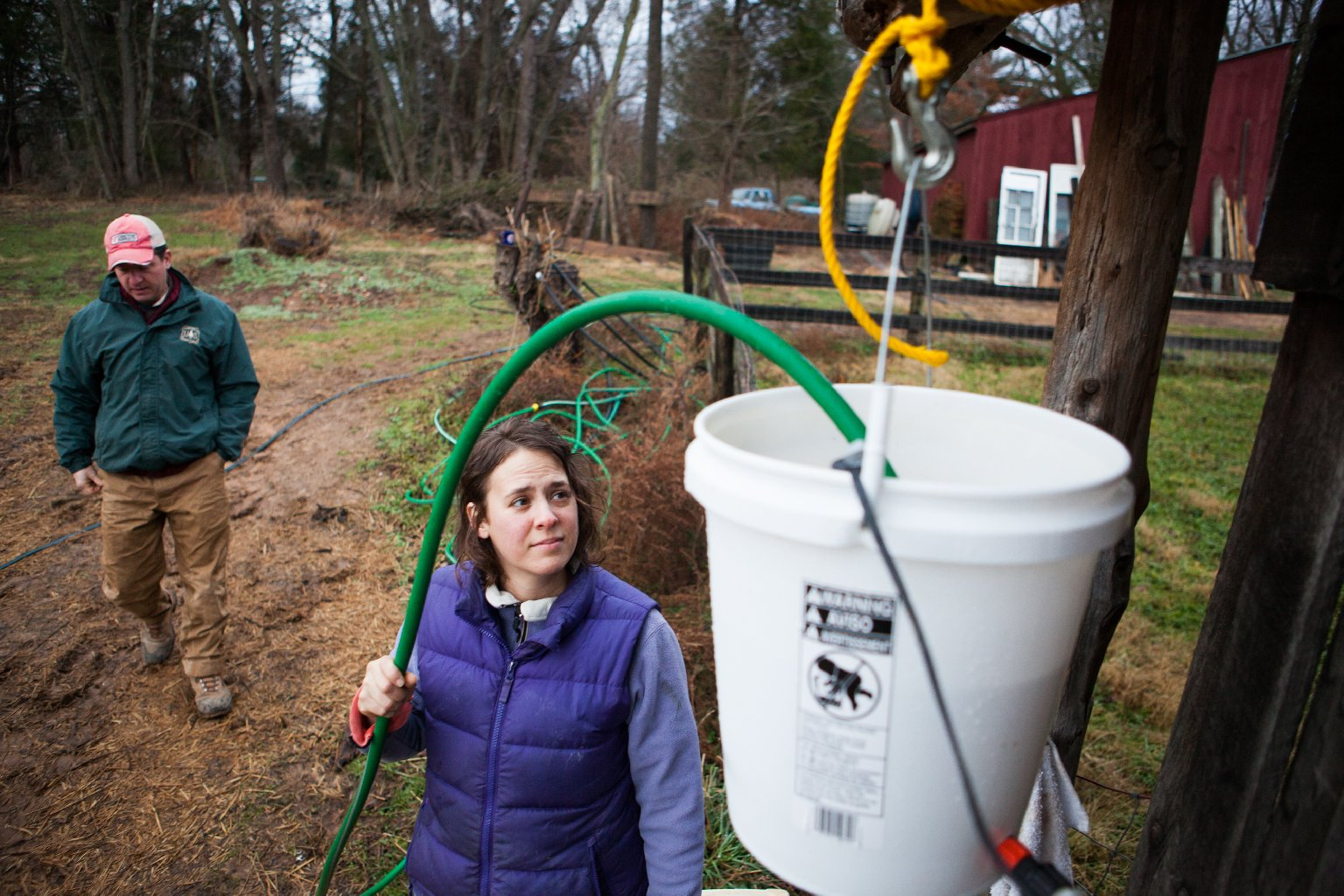 Sara Guerre fills the chicken coop's water feeder. The Guerres installed an aquarium heater to prevent freezing throughout the winter months. Photo: Zac Visco for NPR
