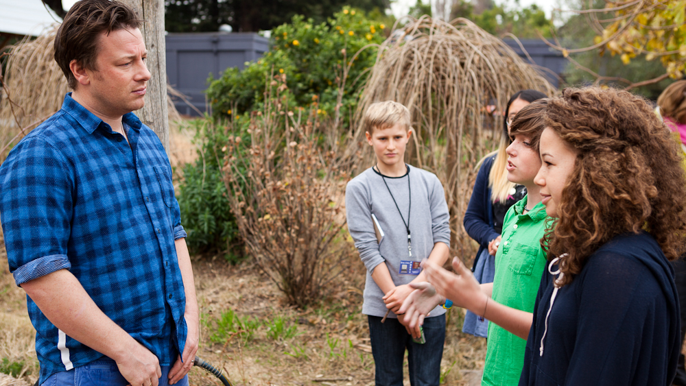 Jamie Oliver listens to students talk about the program in the garden. Photo: Erin Scott