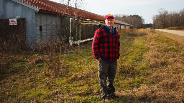 Benny Bunting, a farm advocate for Rural Advancement Foundation International-USA, in front of one of his old chicken houses in Oak City, N.C. Photo: Dan Charles/NPR