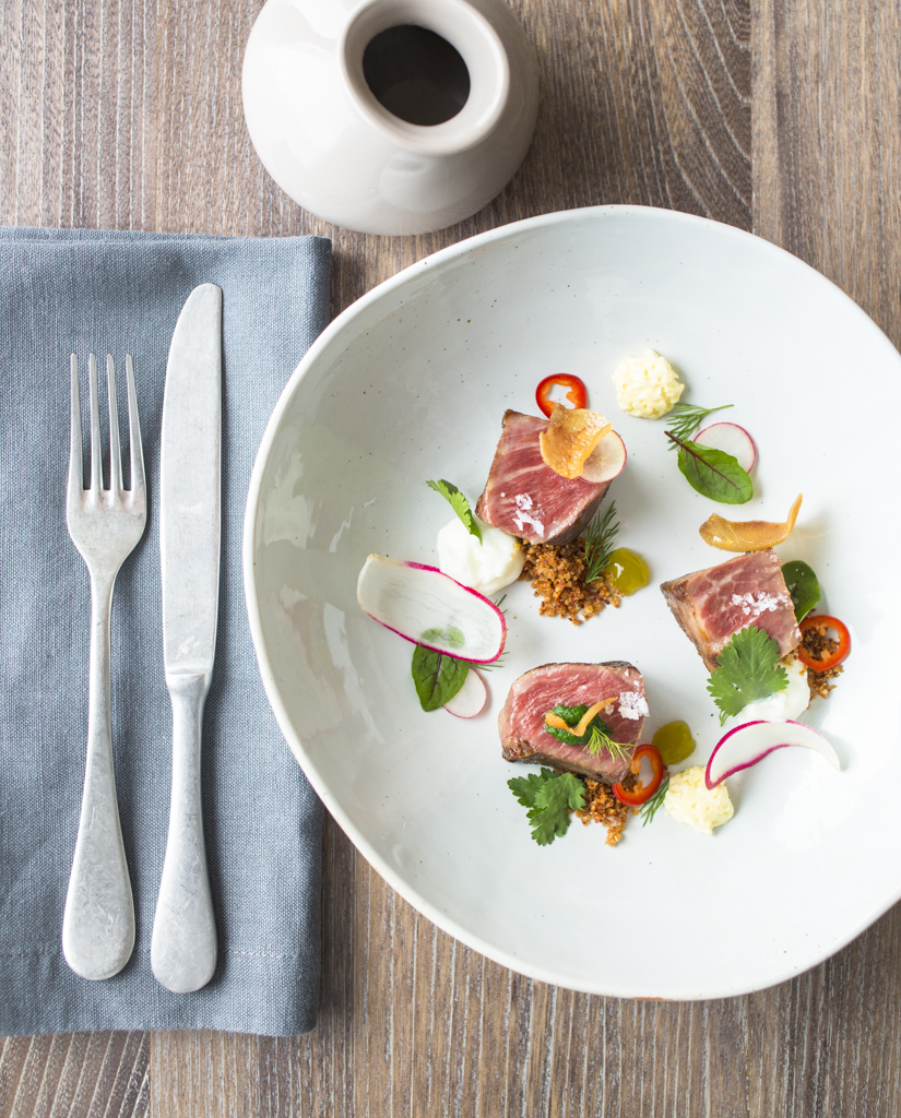 Iberico pork with pig ear, buttermilk curd and ranch consommé. Photo: Eric Wolfinger Photography.