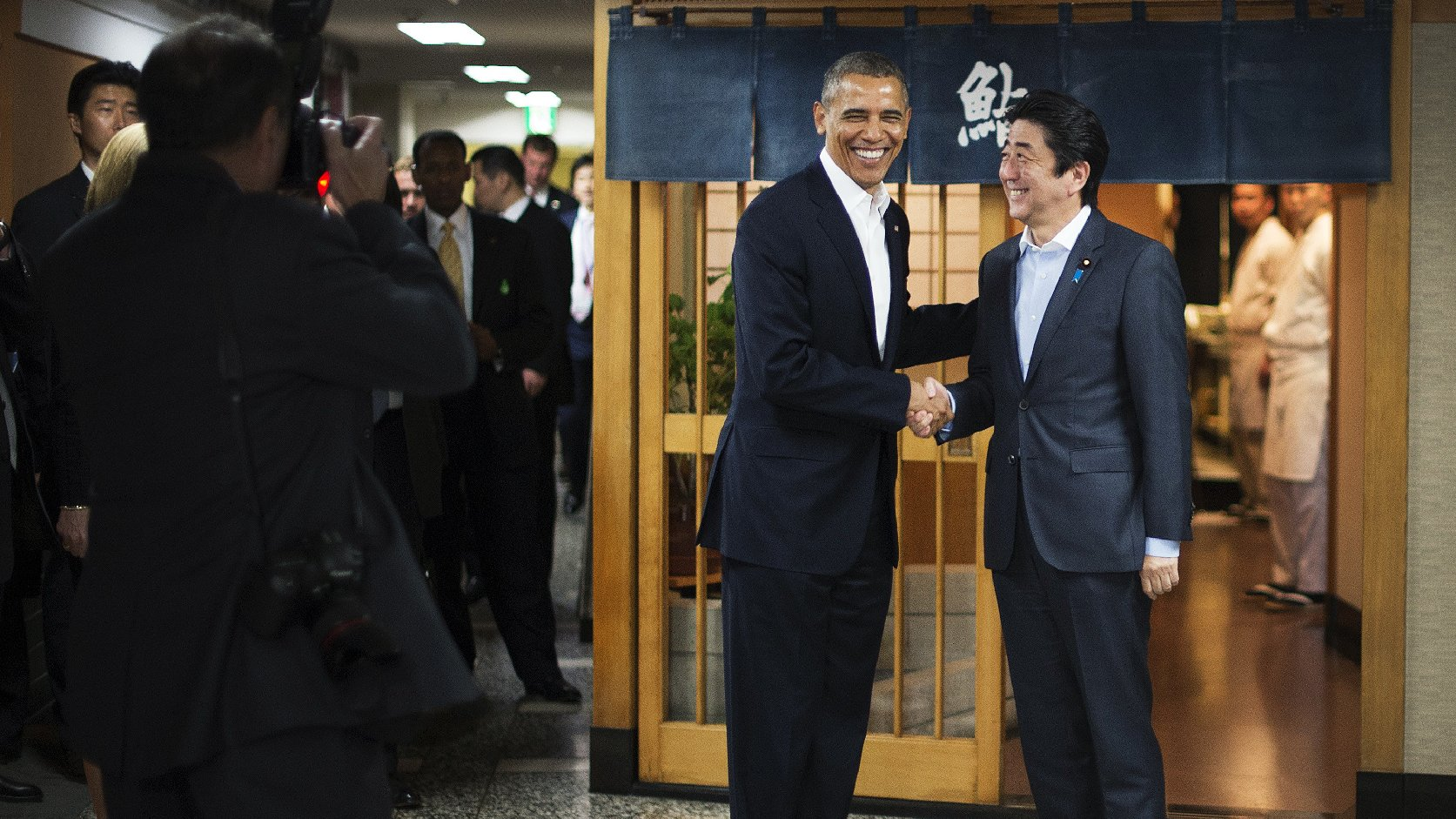 President Obama shakes hands with Japanese Prime Minister Shinzo Abe before a private dinner at Sukiyabashi Jiro restaurant in Tokyo on Wednesday. At Sukiyabashi Jiro, people pay a minimum $300 for 20 pieces of sushi chosen by the patron, Jiro Ono. Photo: Jim Watson/AFP/Getty Images