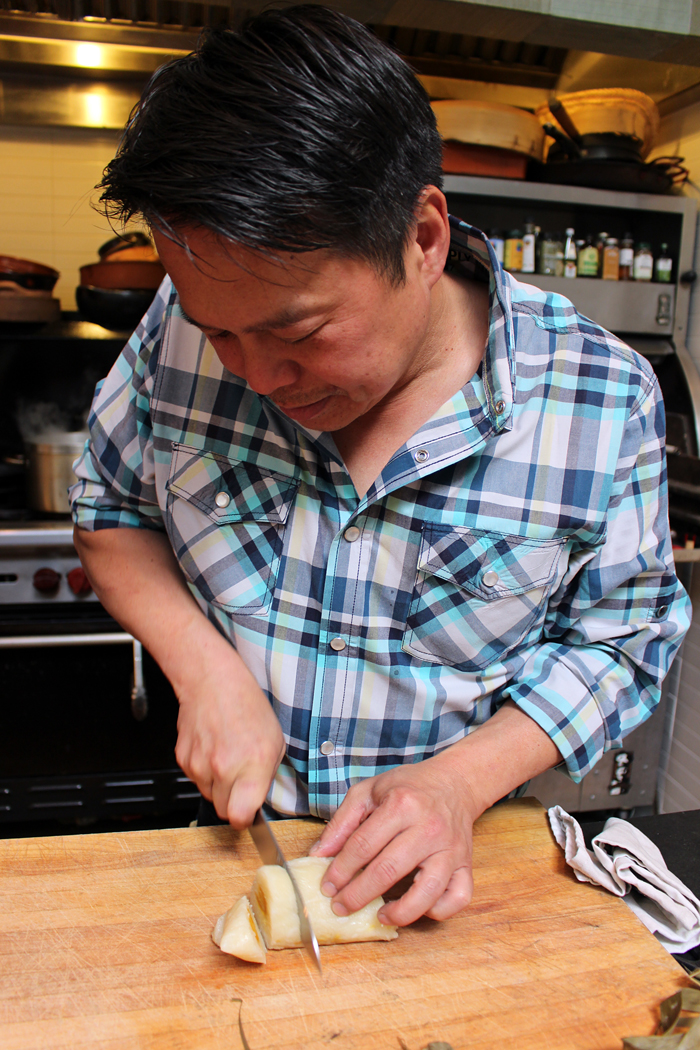 Charles Phan slicing banh chưng to saute. Photo: Wendy Goodfriend