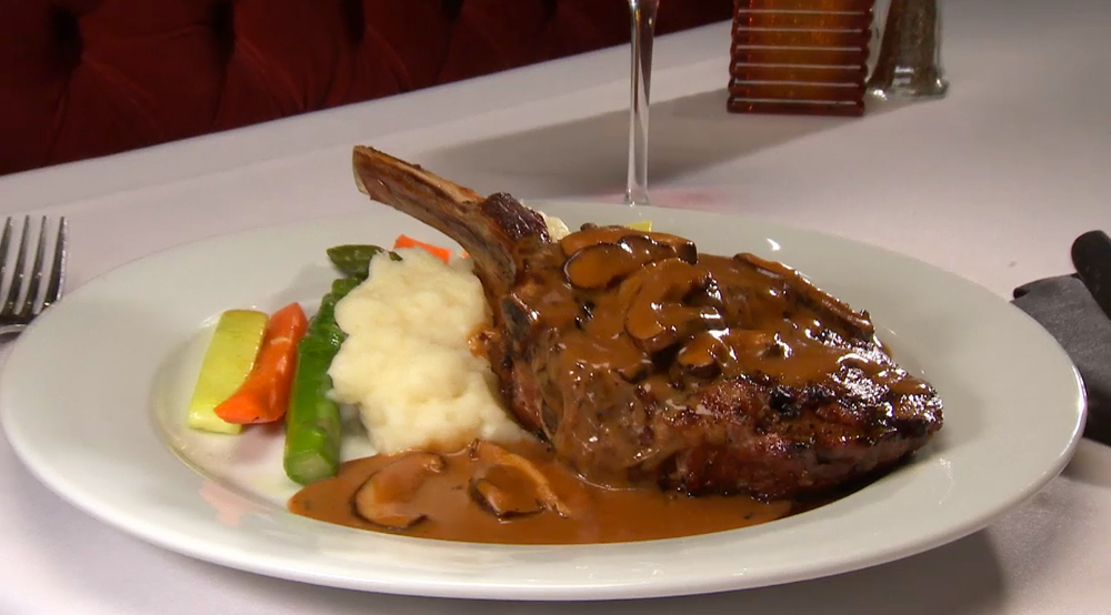 Massimo's Marinated Veal Chop with mushroom sauce served with garlic mashed potatoes and fresh vegetables