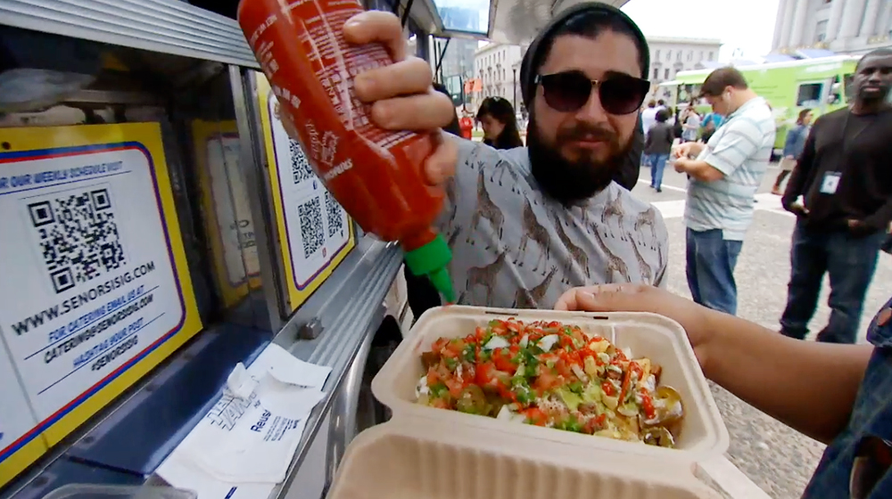 Señor Sisig food truck customer embellishes meal with Sriracha sauce
