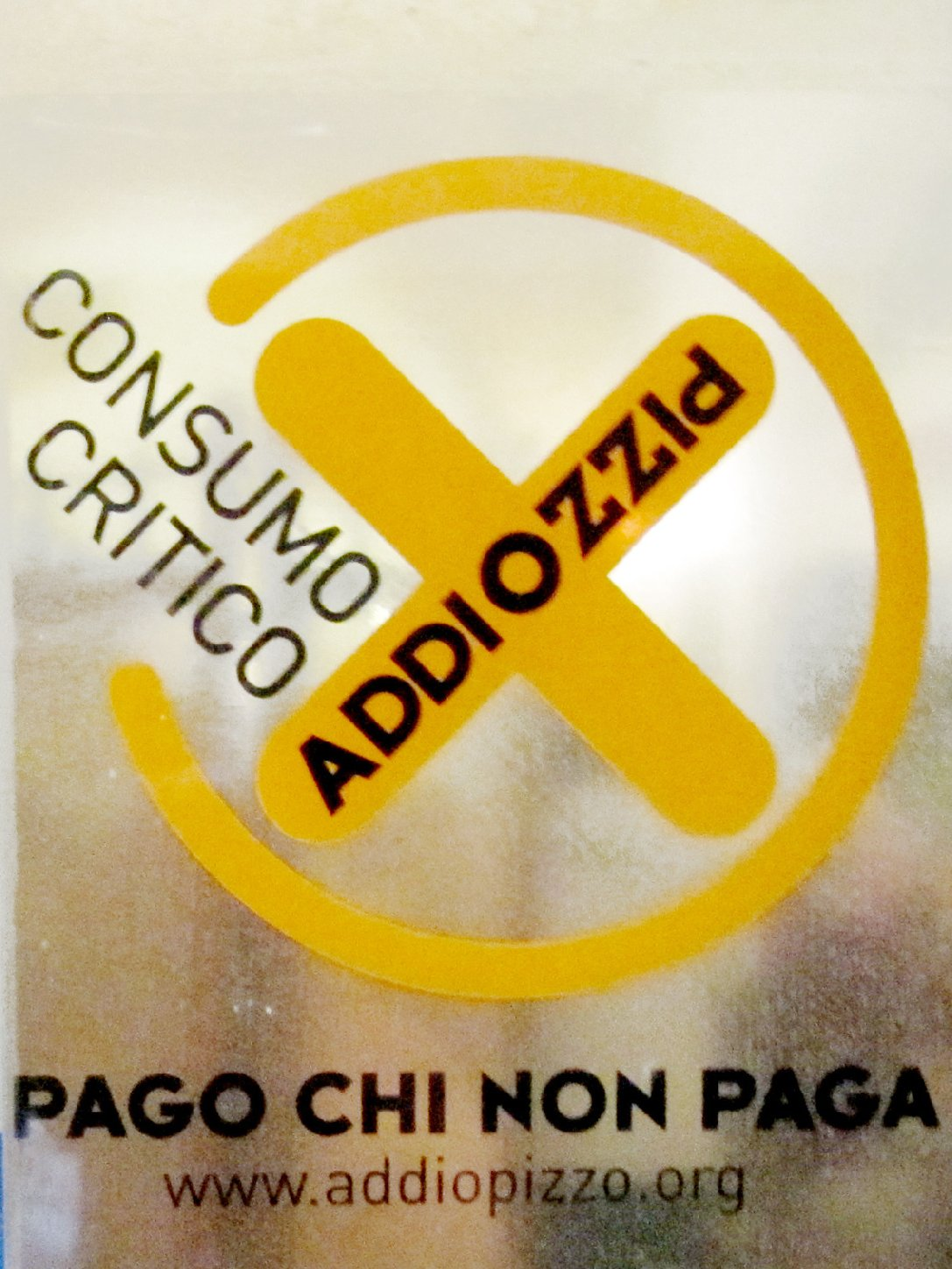 The Addiopizzo sticker on the door of a restaurant or hotel in Sicily tells you the establishment does not pay extortion money to the Mafia. Photo: The Kitchen Sisters