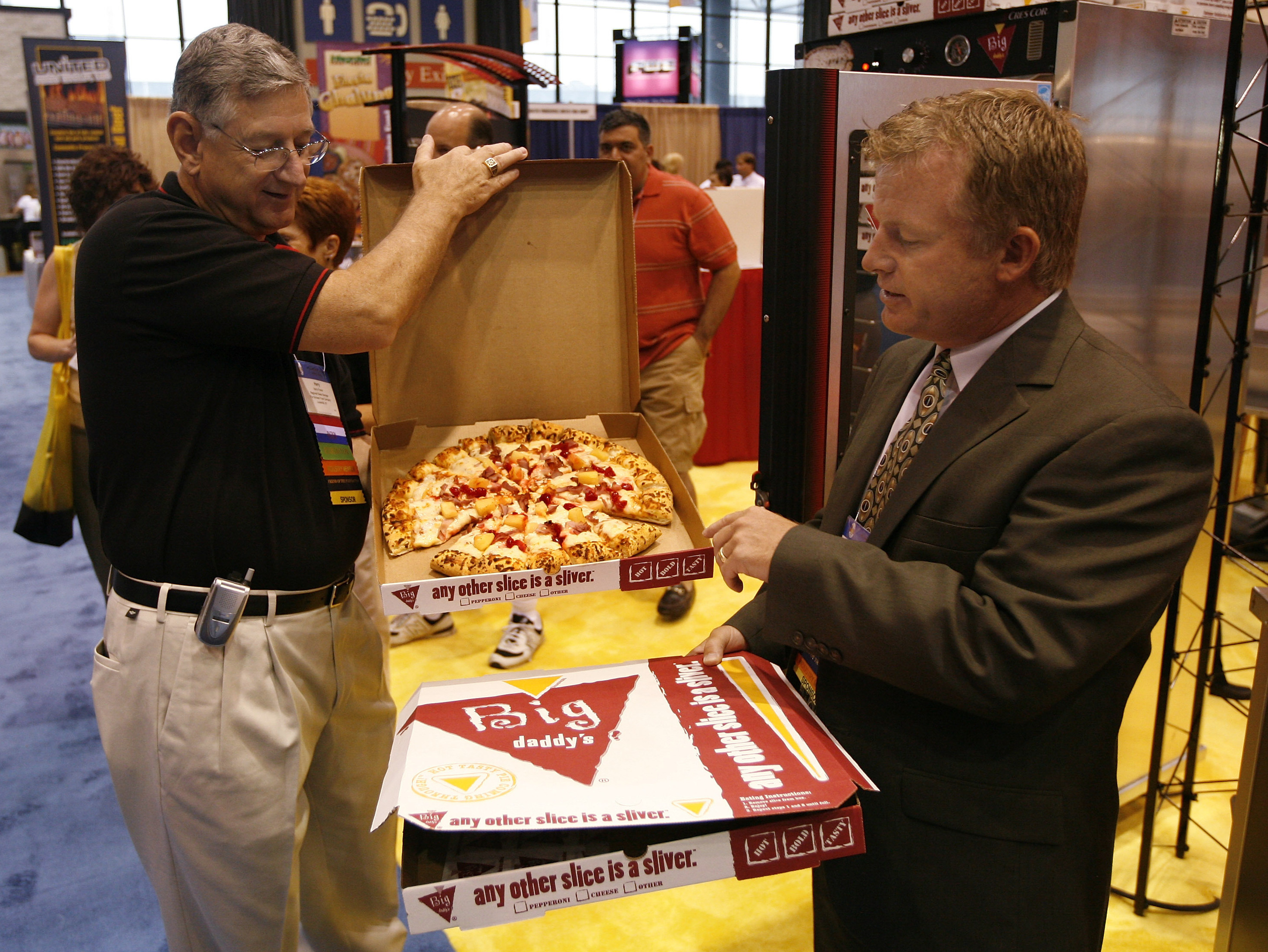 Patrick McCoy (right) and Harry Fowler of the Schwan Food Co. show off their company's Big Daddy's pizza at the School Nutrition Association's national conference in Chicago in 2007. Photo: Brian Kersey/AP