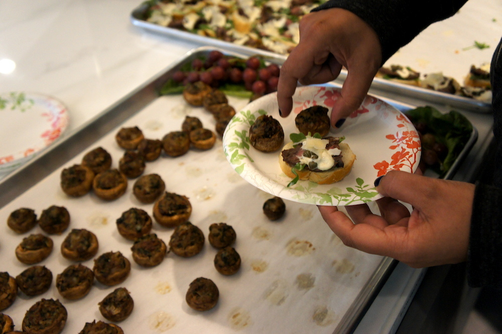 A Yammer employee adds some stuffed mushrooms to her plate. Credit: Angela Johnston