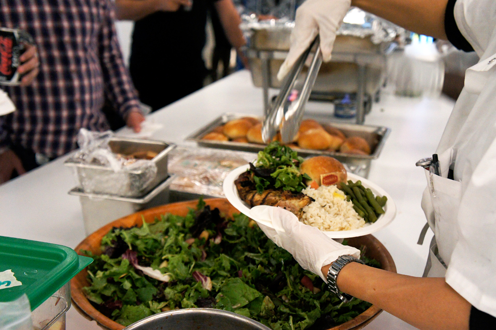 Safia Bubakar serves a meal to an employee at Zendesk. Credit: Angela Johnston