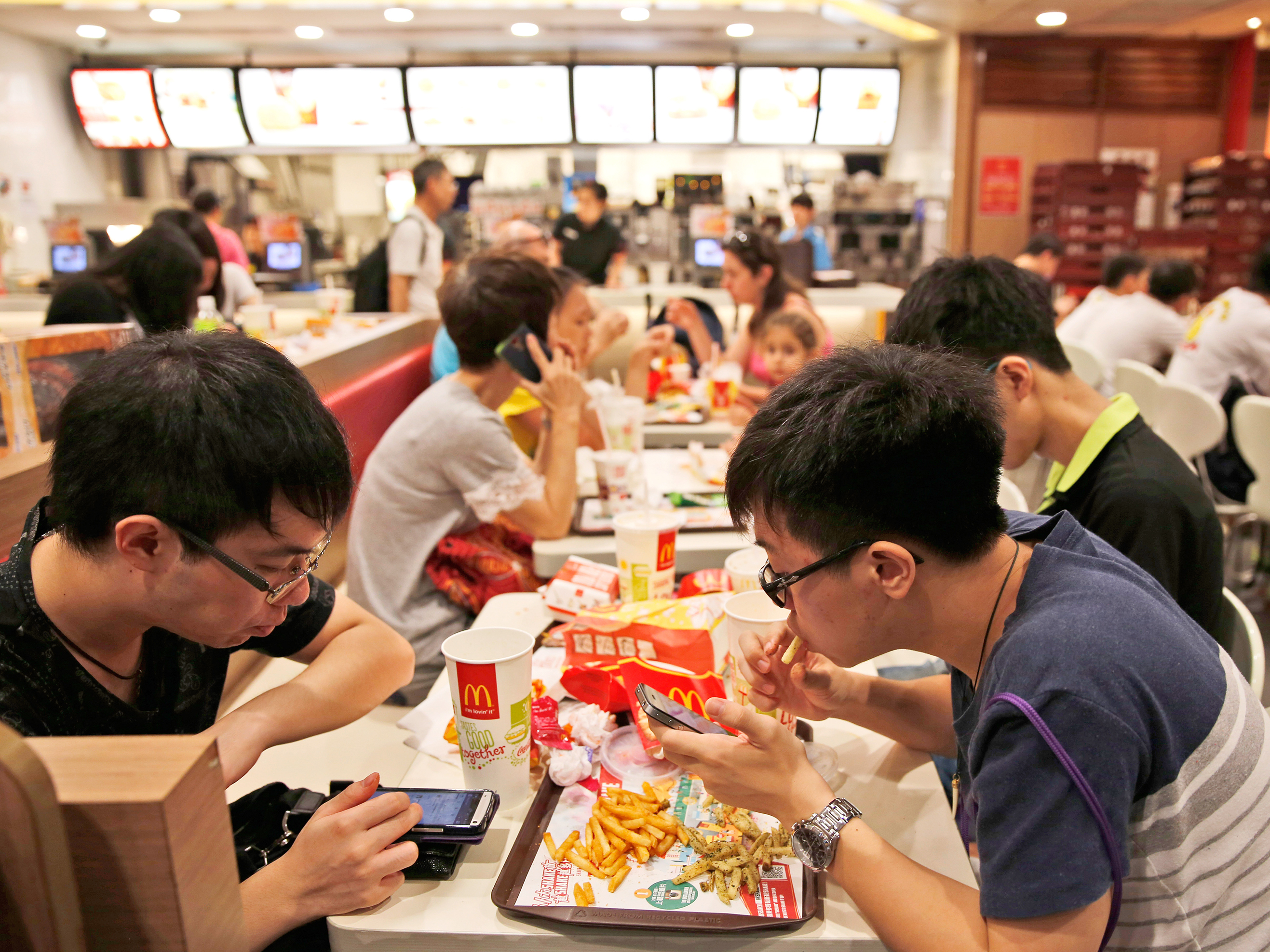 Customers eat at a McDonald's restaurant in Hong Kong Friday, July 25, 2014. McDonald's restaurants in Hong Kong have taken chicken nuggets and chicken filet burgers off the menu after a U.S.-owned supplier in mainland China was accused of selling expired meat. Photo: Kin Cheung/AP