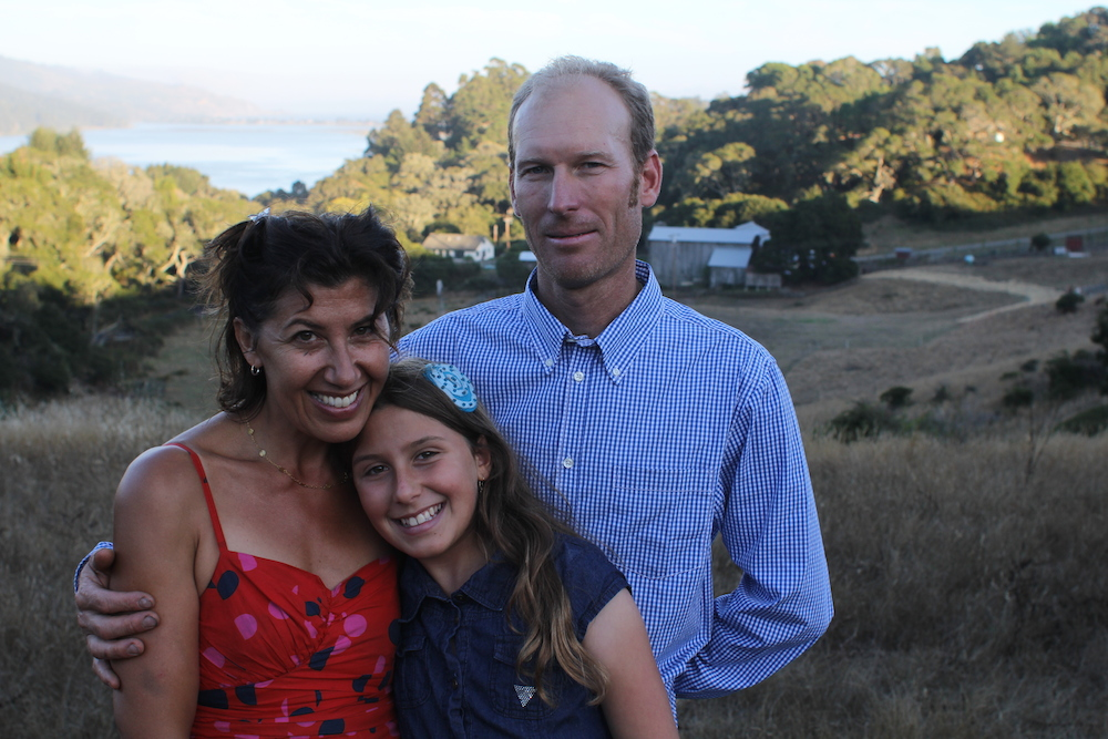 Ed Mann, Amanda Mann and their daughter stand in front of their farm on Horseshoe Hill. Photo: Angela Johnston