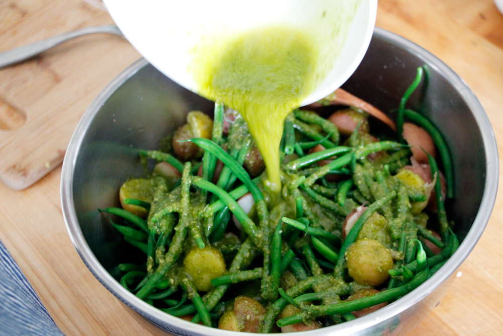 Pour the Lemon-Basil Pesto Vinaigrette over the potatoes and green beans and stir to coat evenly. Photo: Wendy Goodfriend