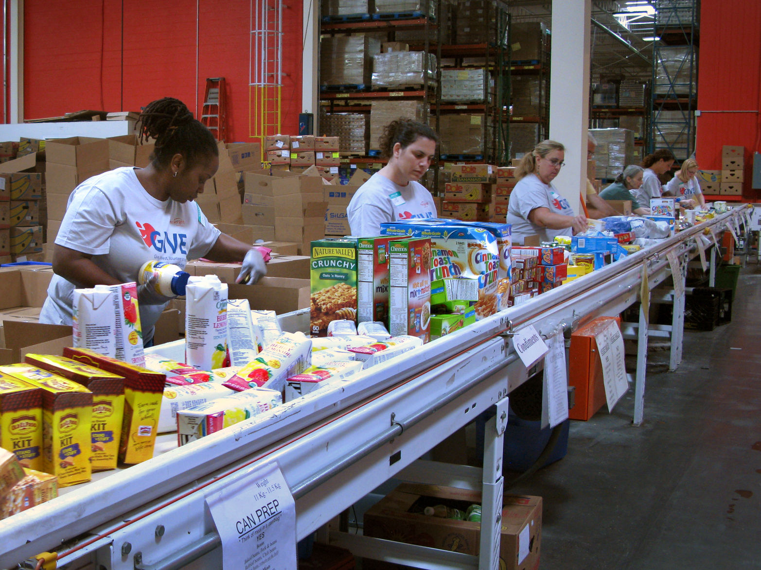 Volunteers at the Maryland Food Bank in Baltimore sort and box food donations on a conveyor belt. The bank started working with groups like the USO in 2013 to provide food aid to families affiliated with nearby military bases. Photo: Pam Fessler/NPR