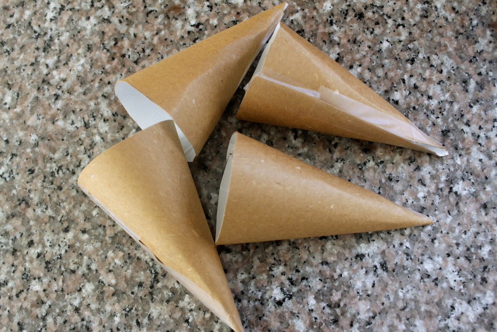 Bring together the straight sides of each quarter to form a cone. Use tape to secure the shape. Cover each cone with aluminum foil. Photo: Kate Williams
