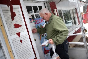 Tom Neville of Catholic Services knocks before entering with a Meals on Wheels delivery to an elderly widow on March 12, in Hainesville, N.J. Photo: John Moore/Getty Images