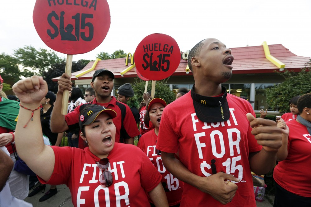 Protesters demonstrate outside a McDonald's in Chicago. Hundreds of workers from McDonald's, Taco Bell, Wendy's and other fast-food chains were expected to walk off their jobs Thursday to push the companies to pay their employees at least $15 an hour, according to labor organizers. Photo: M. Spencer Green/AP