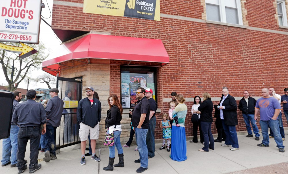 Aficionados line up outside Hot Doug's, a gourmet hot dog diner in Chicago in May 2014. Owner Doug Sohn announced that he will shut the doors in October after nearly 14 years. Photo: M. Spencer Green/AP