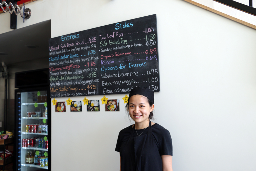 Executive chef and co-owner Stacy Tang in front of the hand-written bento menu at Taiwan Bento. Photo: Kim Westerman