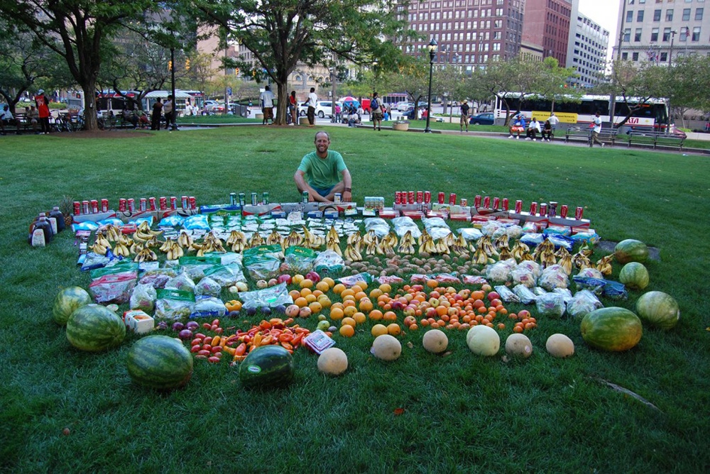 Rob Greenfield has ridden his bicycle across the country, dumpster diving in various cities and making public displays of the food he finds to show how much food is regularly thrown out. Here he is shown with one of his displays in Cleveland, Ohio. Photo: Courtesy of Rob Greenfield