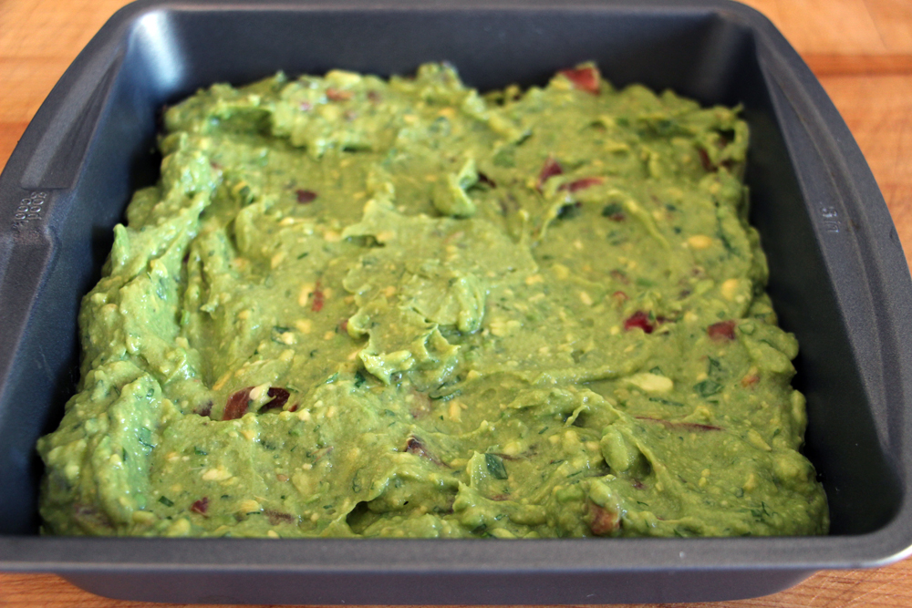 Spread the guacamole in a shallow 9-inch square or round serving or baking dish .