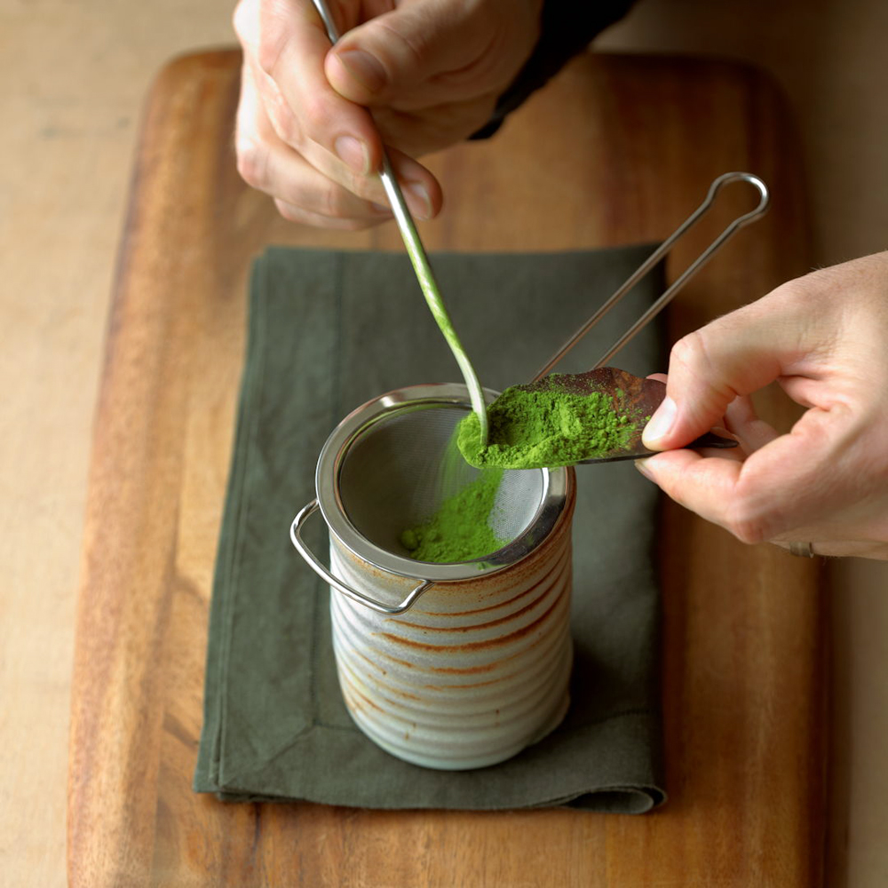 Matcha being sieved into a cup. Image courtesy of Breakaway Matcha