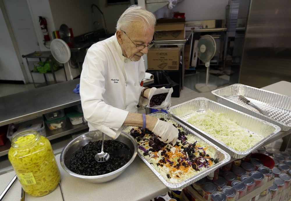 Homeless advocate Arnold Abbott, 90, director of the nonprofit group Love Thy Neighbor Inc., prepares a salad Wednesday in the kitchen of The Sanctuary Church in Fort Lauderdale, Fla. Abbott was recently arrested, along with two pastors, for feeding the homeless in a Fort Lauderdale park. Photo: Lynne Sladky/AP