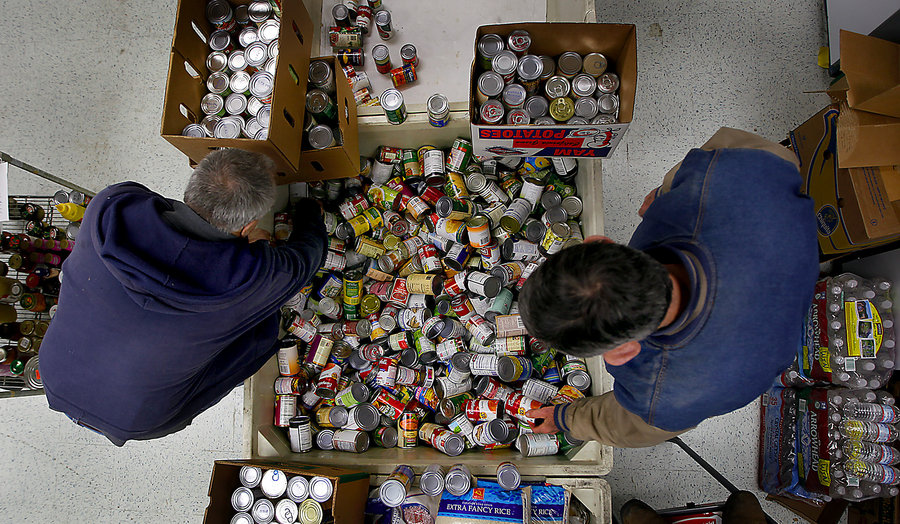John Umland (left) and John Torrens gather donated cans of food in 2011 in Rohnert Park, Calif., for the group Neighbors Organized Against Hunger. Hunger advocates say a lot of nutritionally dense food like canned tuna and beans can be cheaper than processed food.  Photo: Kent Porter/ZUMA Press/Corbis