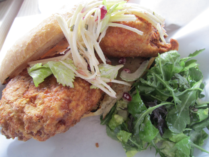 The Fried Chicken: with fish sauce caramel, Old Bay Butter, apple celery leaf slaw, and pomegranate seeds on a French hero roll. Photo: Alix Wall