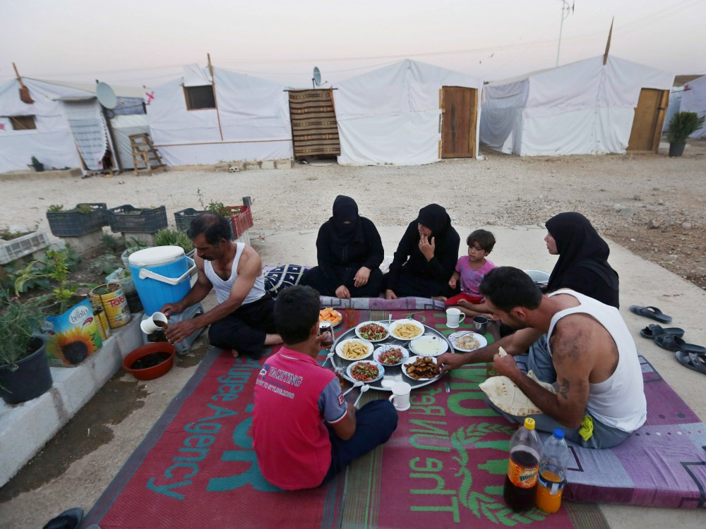 Syrian refugees break their fast outside their tent at a Syrian refugee camp in Marj, Lebanon, on June 29. The World Food Program says it has suspended a food voucher program serving more than 1.7 million Syrian refugees because of a funding crisis. Photo: Bilal Hussein/AP