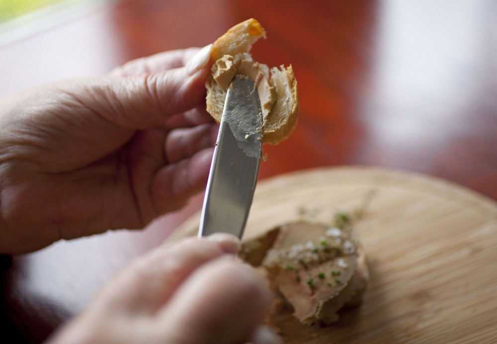 Karlene Bley of Los Angeles spreads her torchon of foie gras onto bread during lunch at the Presidio Social Club restaurant in San Francisco. Last week, a federal judge overturned California's ban on the dish. Photo: Eric Risberg/AP