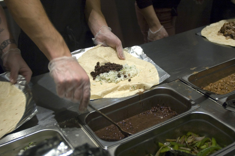 Workers prepare burritos at a Chipotle Mexican Grill in New York. The restaurant chain has stopped serving pork in about one-third of its U.S. locations.  Photo: Richard Levine/Demotix/Corbis