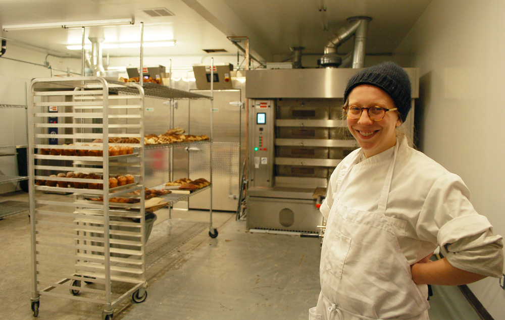 Avery Ruzicka now oversees a crew of four in the new 3,000-square-foot production facility, featuring the big Italian oven behind her. Photo: Susan Hathaway