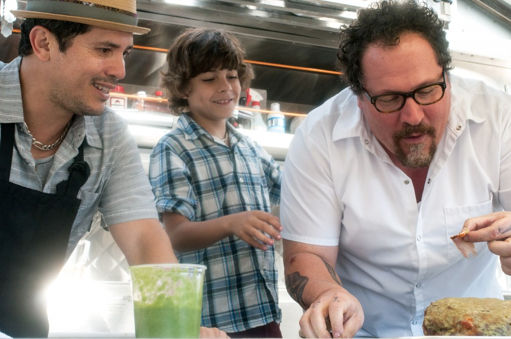 In Chef, Jon Favreau (right) plays a chef who leaves his post at a respected LA restaurant to launch a food truck with his son (Emjay Anthony, center) and a former line cook (John Leguizamo). Photo: Merrick Morton/Courtesy of Open Road Films