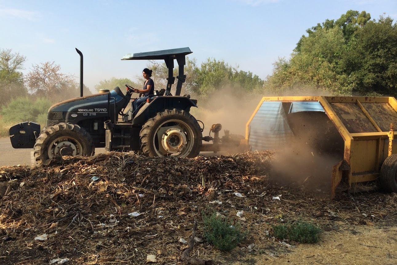 Former Director Nidhi Solanki of Project Compost uses a tractor and compost turner to turn food waste into compost. Photo: Sequoia Williams