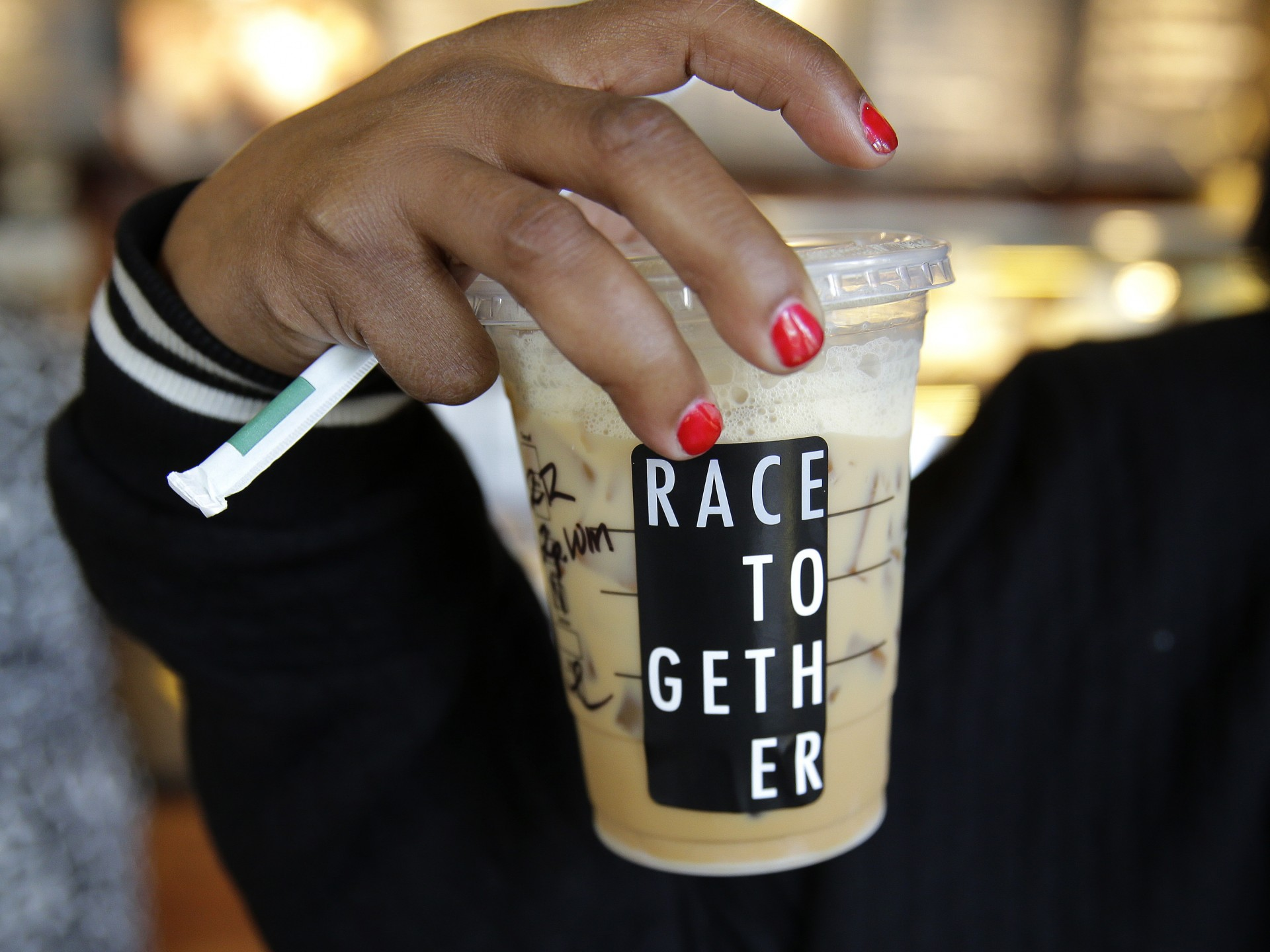 "Larenda Myres holds an iced coffee drink with a ""Race Together"" sticker on it at a Starbucks store in Seattle. Starbucks baristas will no longer write ""Race Together"" on customers' cups starting Sunday. Photo: Ted S. Warren/AP"