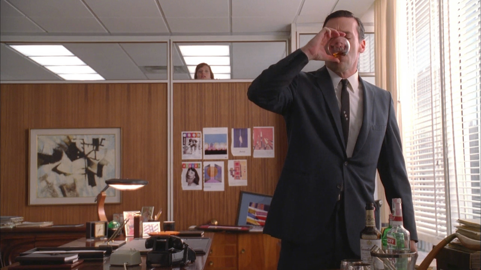 Don (Jon Hamm) downs a drink in the office, spied on by Peggy Olson (Elisabeth Moss.) (Photo: AMC)