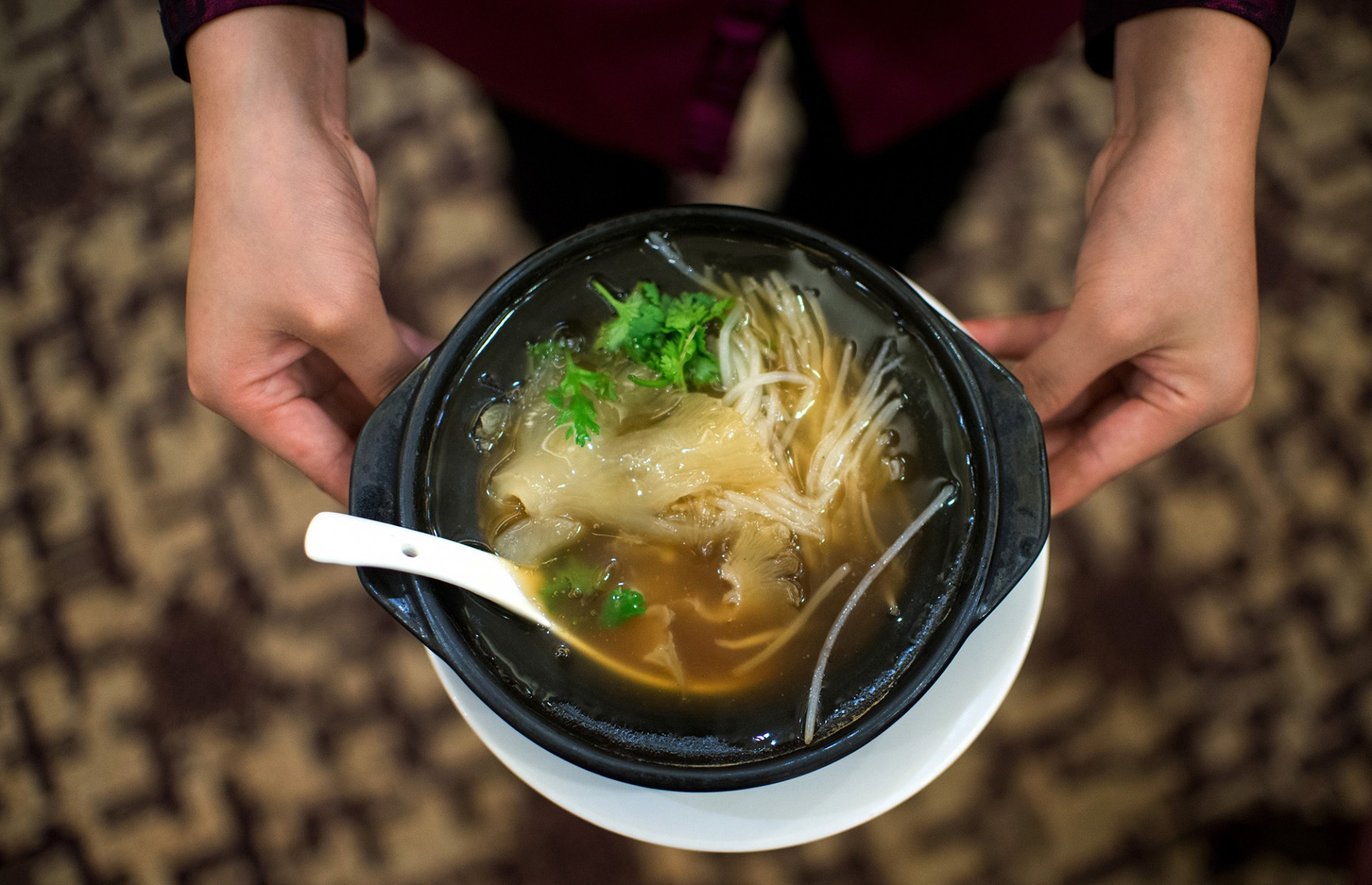 A waitress serves shark fin soup in a restaurant in Guangzhou, in southern China's Guangdong province on Aug. 10, 2014. Photo: Johannes Eisele/AFP/Getty Images