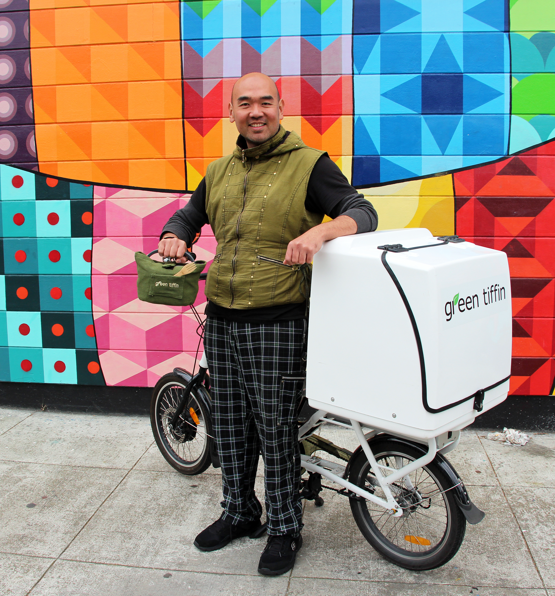 Adrian Tay, founder/owner of Green Tiffin with electric delivery bike and tiffin meal