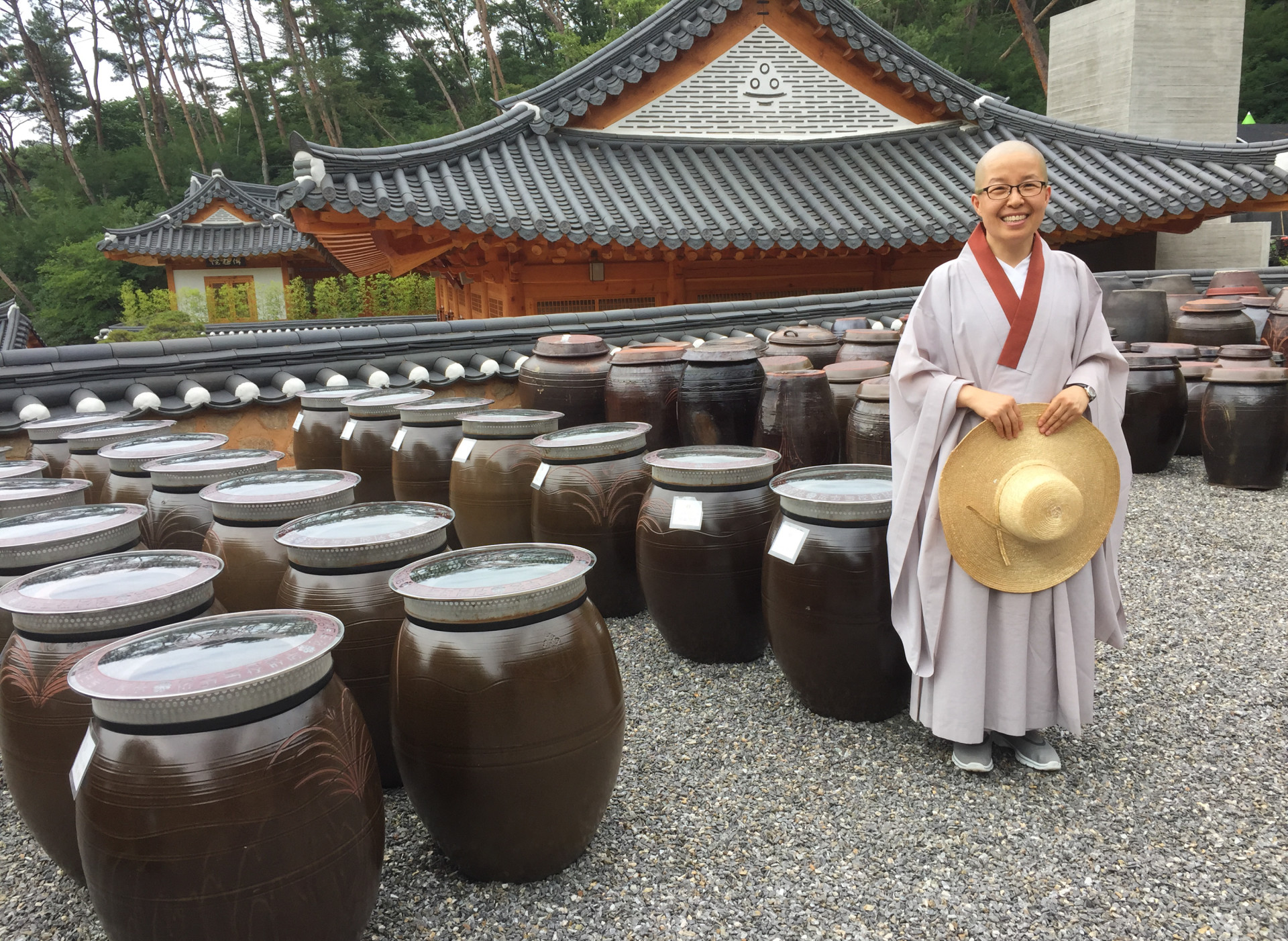 Sun Woo directs the visitor program at Jingkwansa, a Buddhist temple outside Seoul famous for preserving the art of Korean temple food. Behind her are giant jars filled with fermented soybeans.