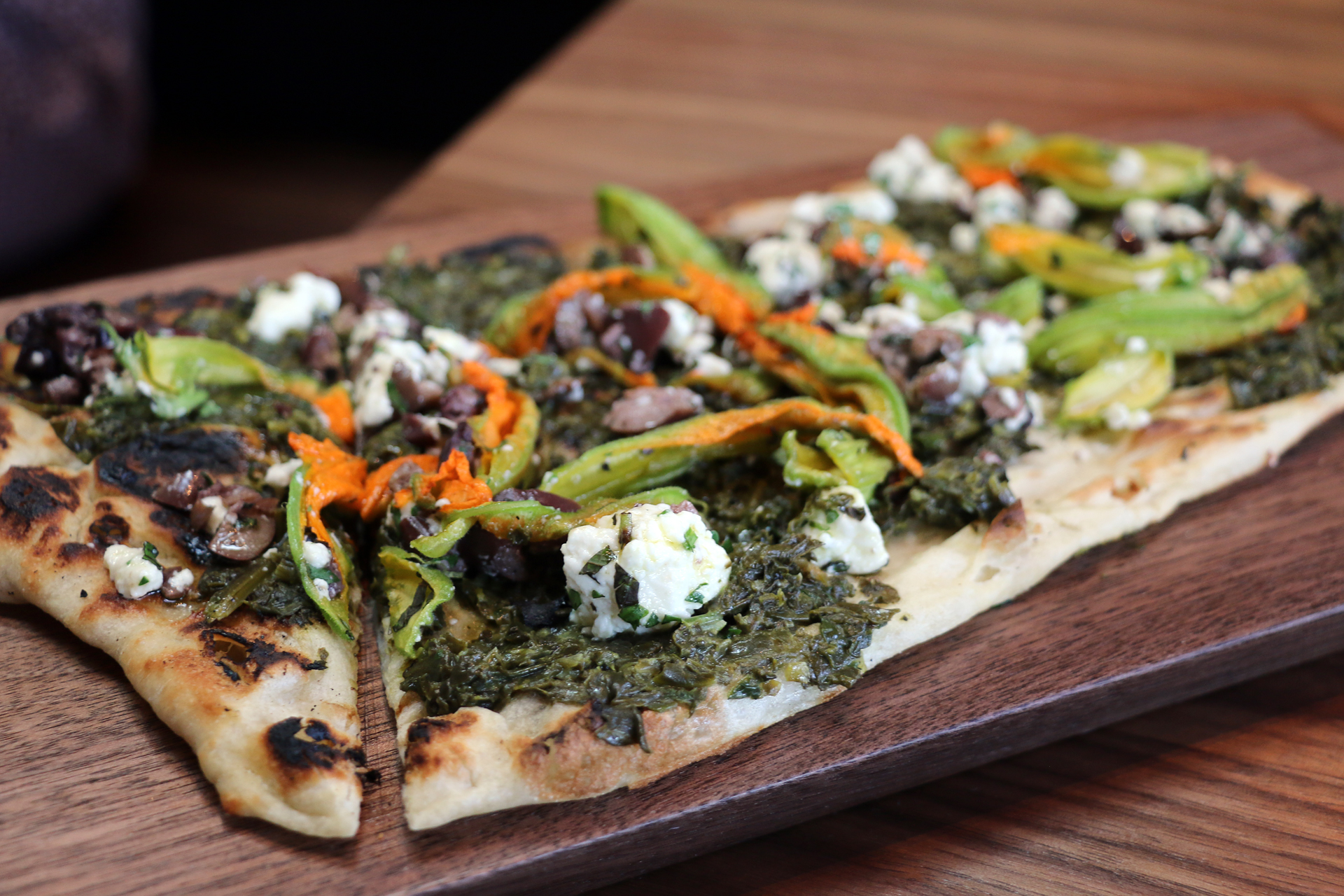 Flatbread with spinach, feta, squash blossoms, and olives from the wood-burning oven.