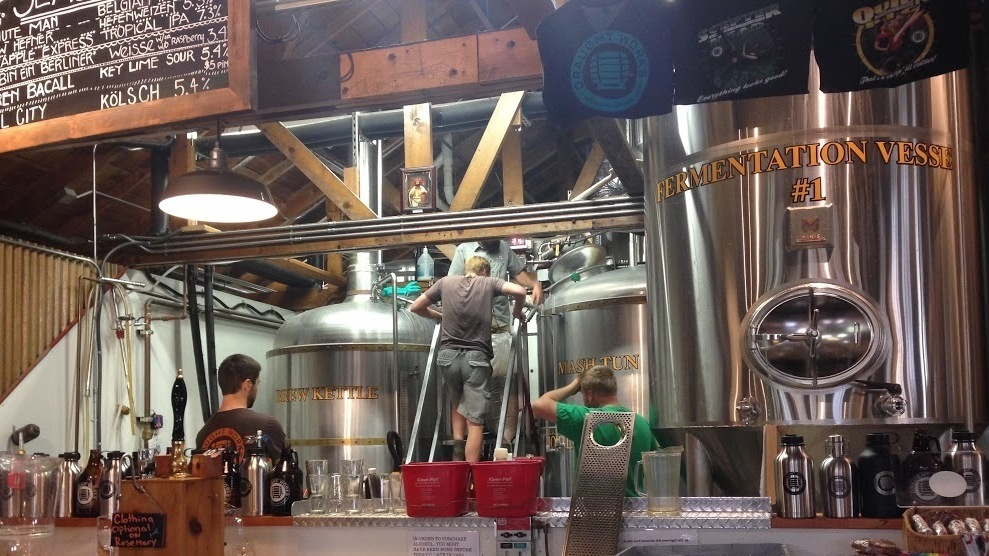 Brewers from Draught Works and the Denver Beer Co. collaborate on making a huckleberry sour beer last weekend at the Draught Works brewery in Missoula, Mont. The beer was kettle soured before being added to the fermentation tank seen here.