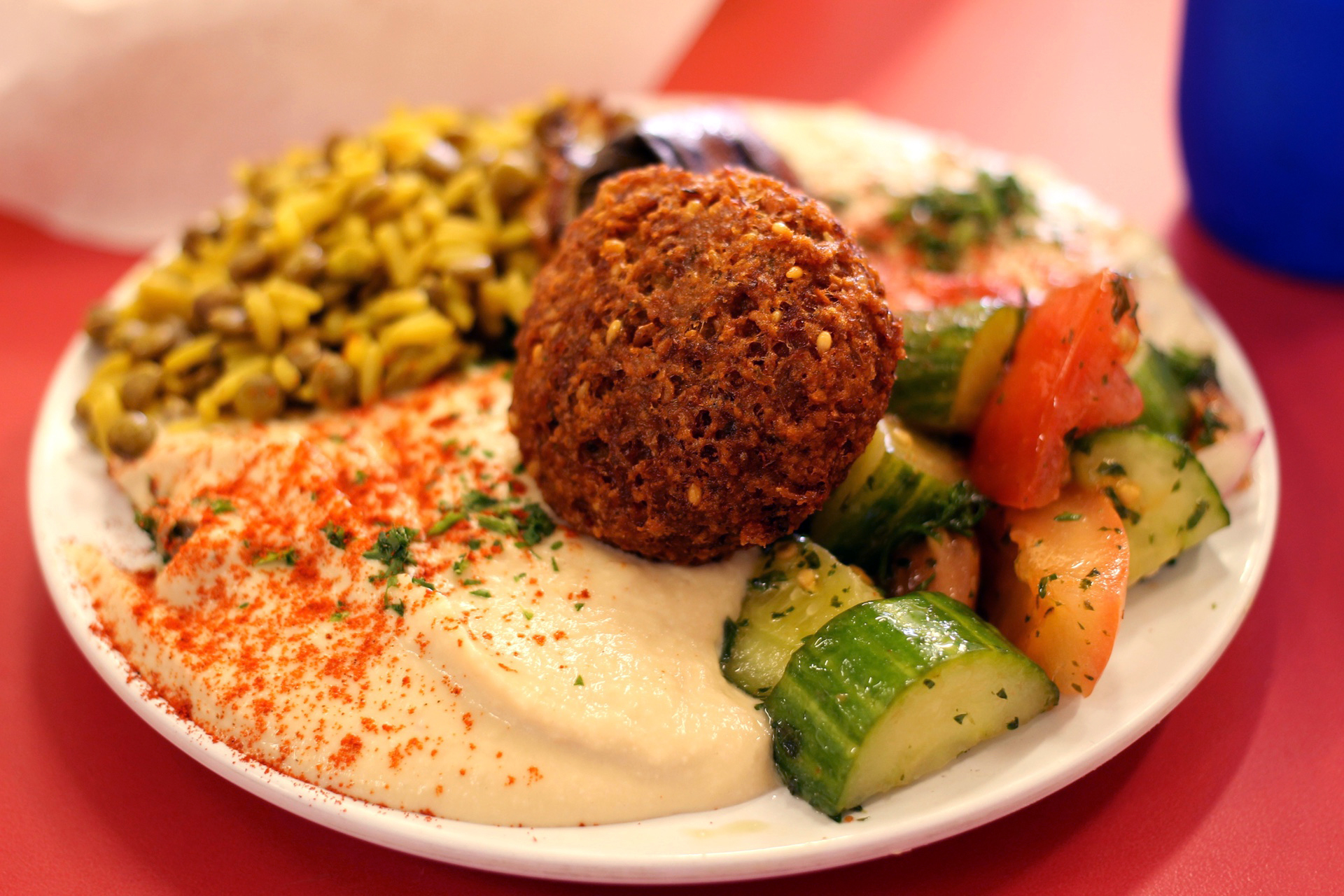 The vegetarian plate at Sunrise Deli in San Francisco includes falafel, hummus, cucumber salad, one dolma, lentils and rice.