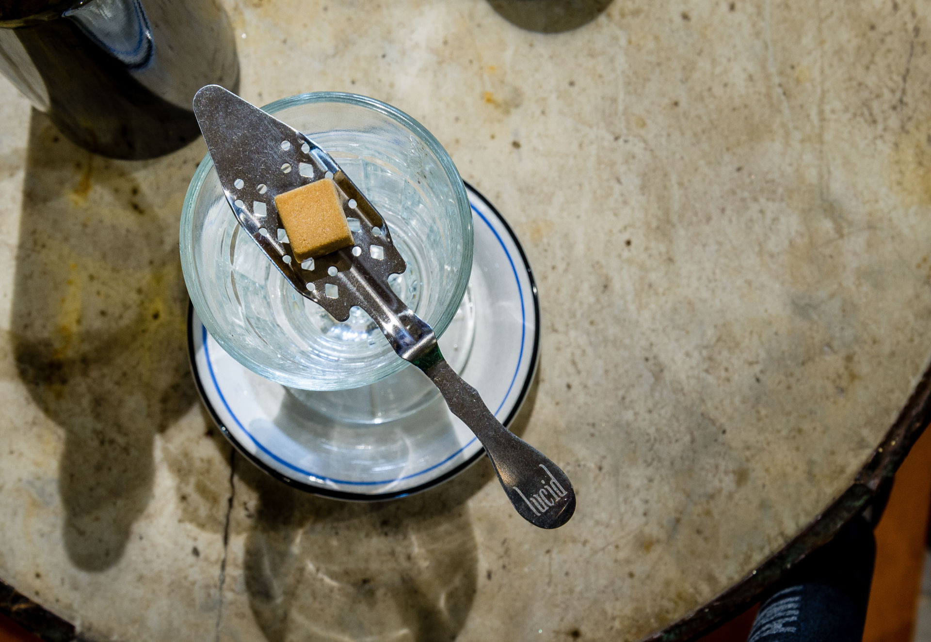 A sugar cube is cradled by a slotted spoon balanced on top of a glass of absinthe.