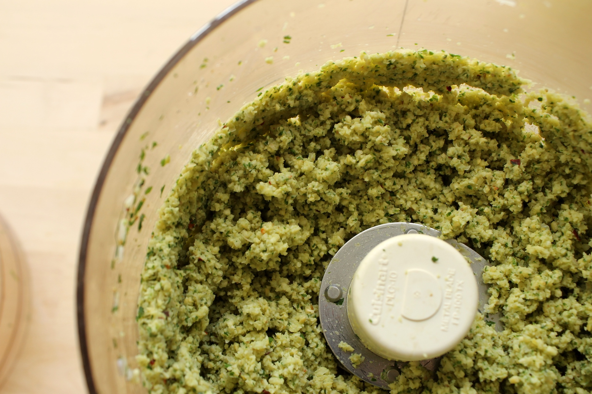 The processed falafel mixture should be a coarse paste. You want it to stick together, but you also want to have small pieces of chickpeas throughout.