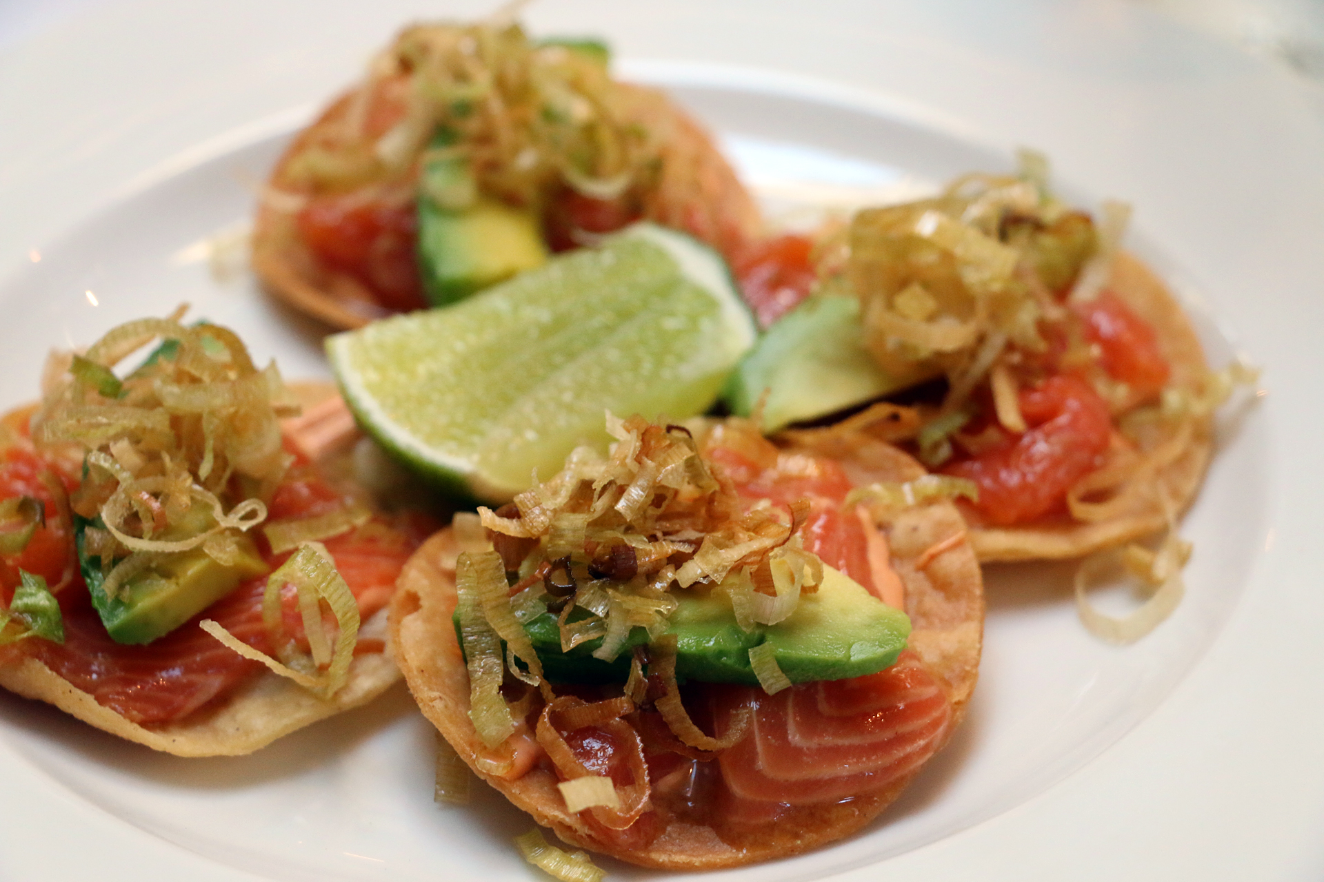 Trout tostadas with chipotle sauce and fried leeks.