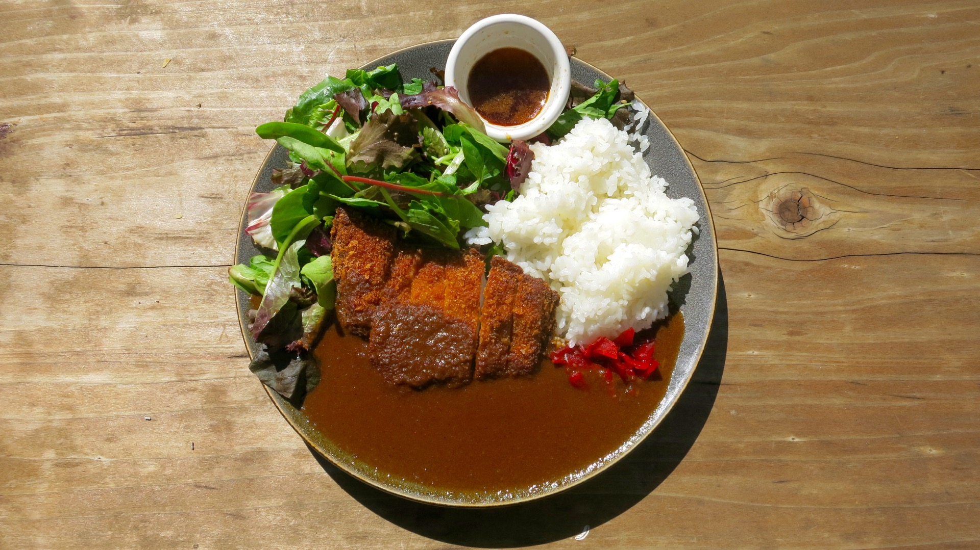 Juicy pork tonkatsu swims in a pool of savory curry sauce from AS B-Dama.