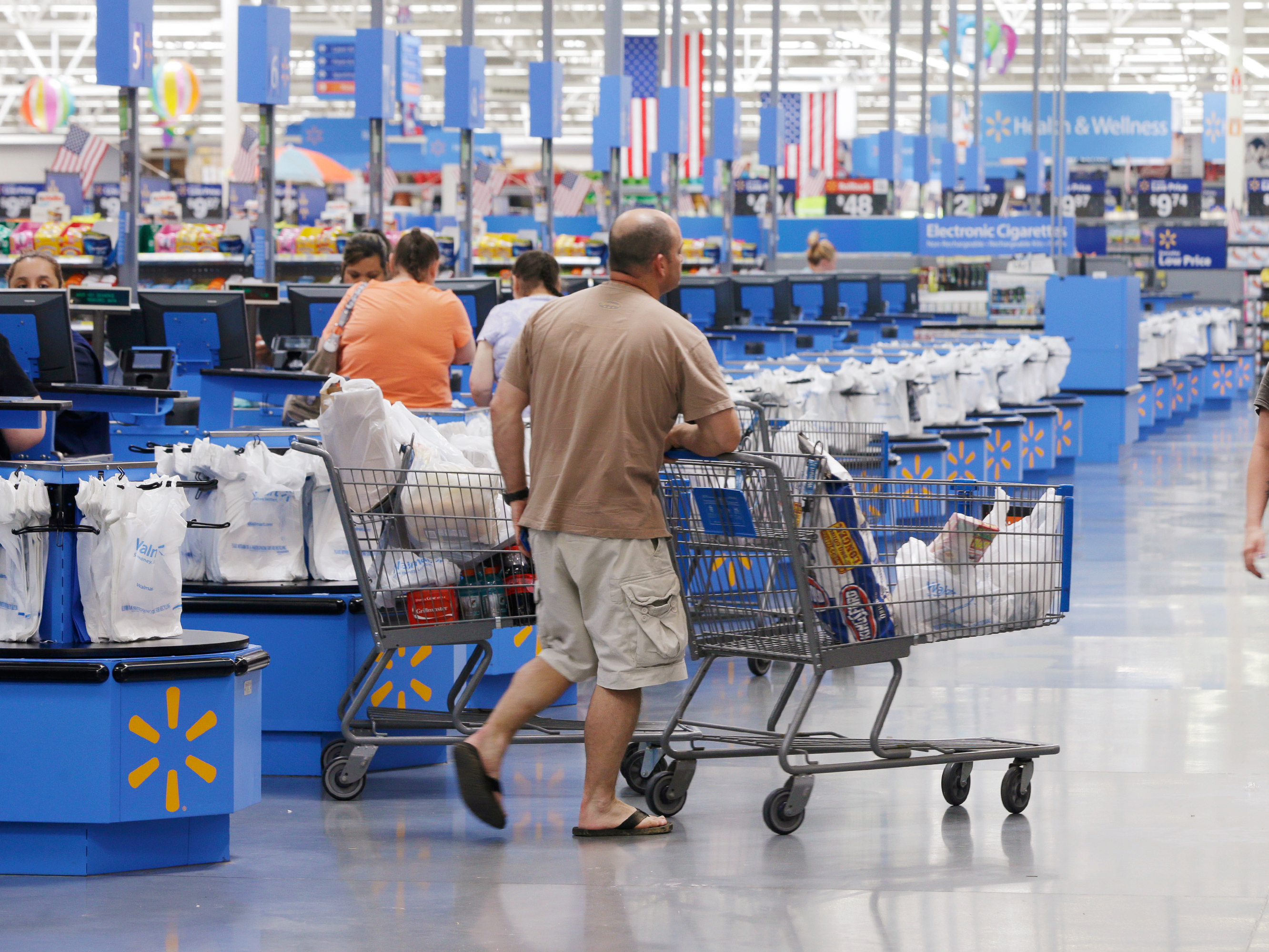 Shoppers walks from the checkout at a Walmart Supercenter store in Springdale, Ark., Thursday, June 4, 2015.