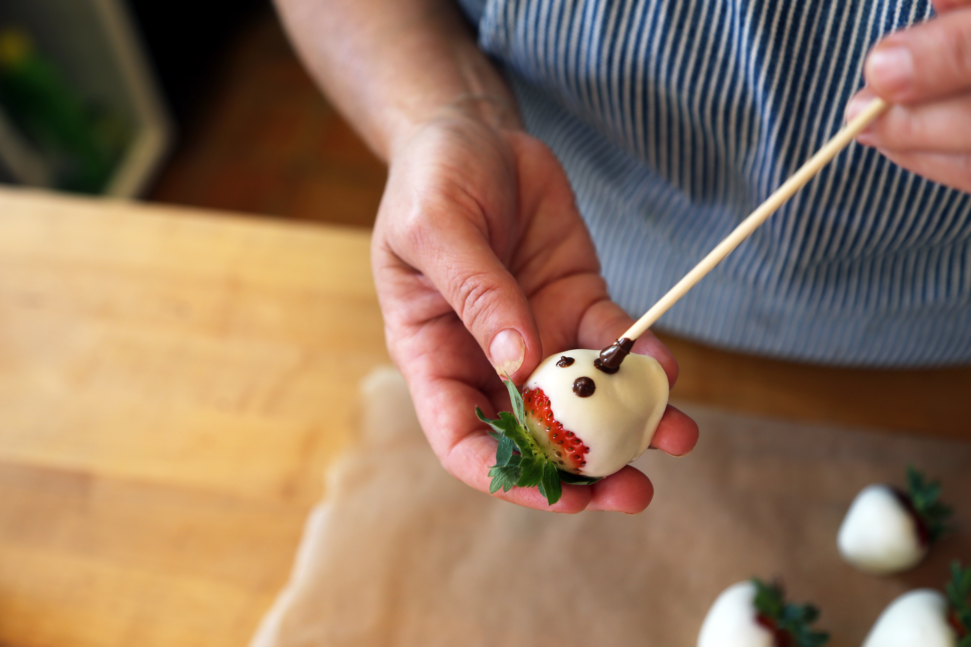 Using a toothpick or wooden skewer, draw eyes and a ghoulish mouth on each strawberry.