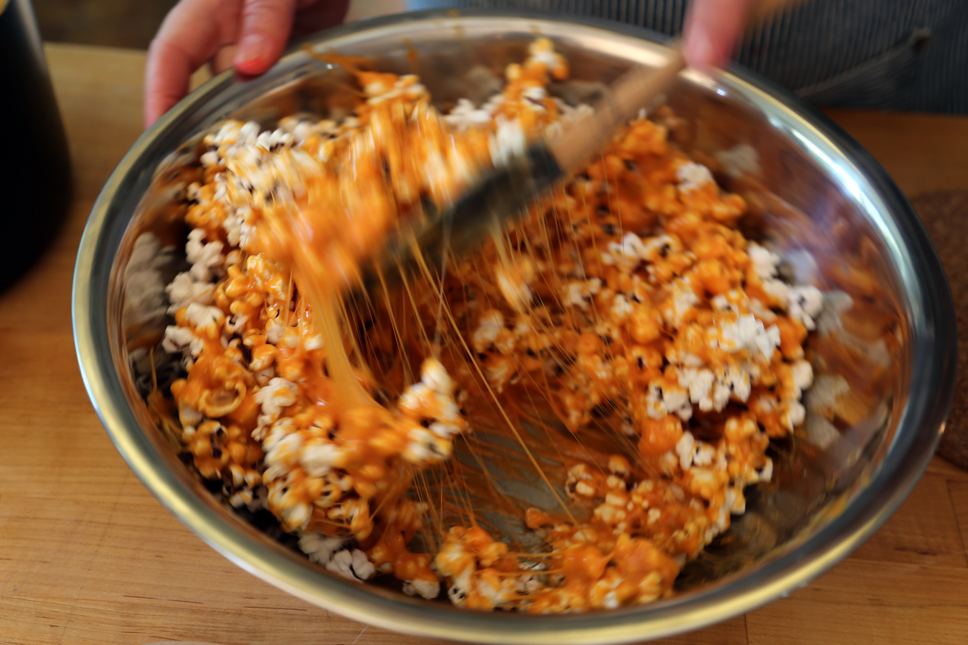 Pour the caramel mixture over the popcorn and stir to completely coat the popcorn.